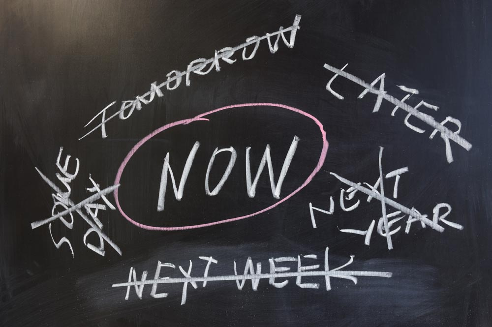 "Chalkboard concept of procrastination with the word ""Now"" circled."